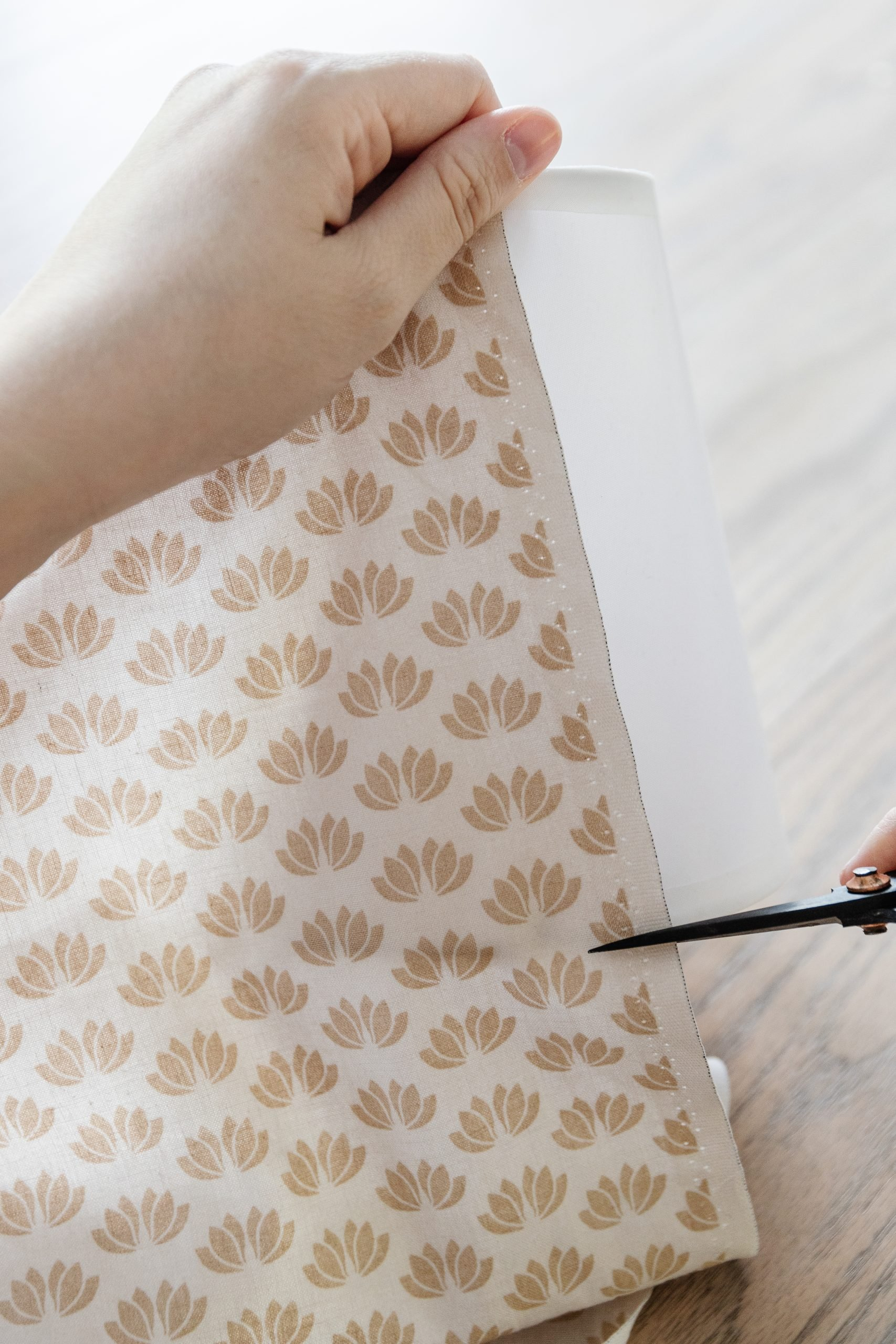 """Cut your fabric, so it's only 1"""" longer than your lampshade. You will trim off the extra fabric at the very end, but it's nice to have extra fabric just if you are working with a tapered lampshade. Start by making your first pleat. You want to place your glue on the very inside edge of the pleat and push it down, so it sticks to the lampshade. Once that has dried, move to the bottom part of the pleat and do the same. Do this same process over and over again until you've completed the lampshade. Make sure you're aware of how much fabric is on each end of the lampshade. You want to keep it centred. Once you're done, trim off all the excess material on the top and bottom, so it's flush with the lampshade edge. To create a """"finished"""" look, I used two stretchy elastic pieces and wrapped them in the material. Glue it on the edge of the lampshade - and you're done!"""